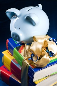 Photo of stack of books wrapped with a ribbon and bow with a blue piggy bank on top.
